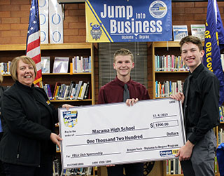 Oregon Tech business professor Sharon Beaudry presents a check for $1,200 from Oregon Tech to Mazama's FBLA program. Accepting the check are Nathan Hantzmon, FBLA president; and Dakota Powless, FBLA vice president of finance.